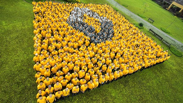 Renault staff forming Renault logo  in two tones on grass - Renault Oman